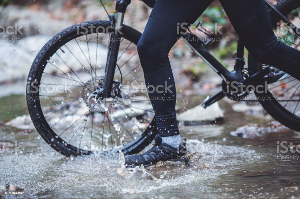 Man is crossing the river with his bicycle because there no other way...