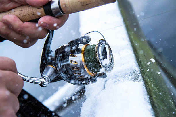 Extreme winter fishing Fishing reel in very cold weather. fishing reel stock pictures, royalty-free photos & images