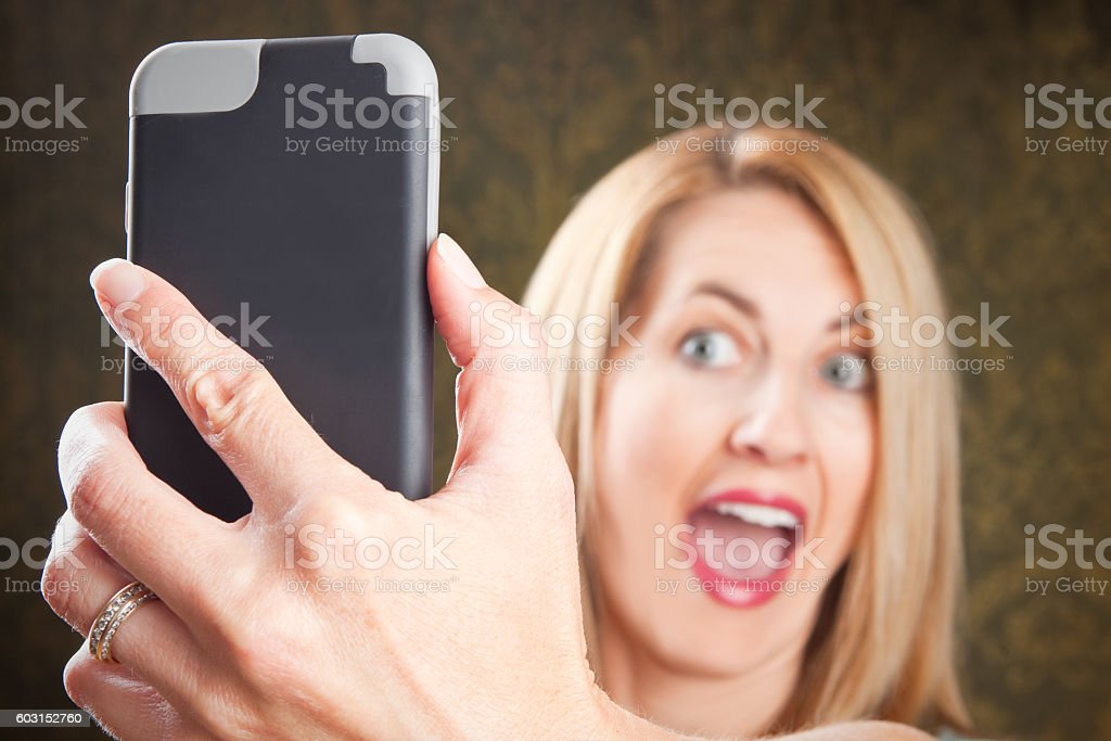 Extremely Cheerful WOman Taking Selfie stock photo