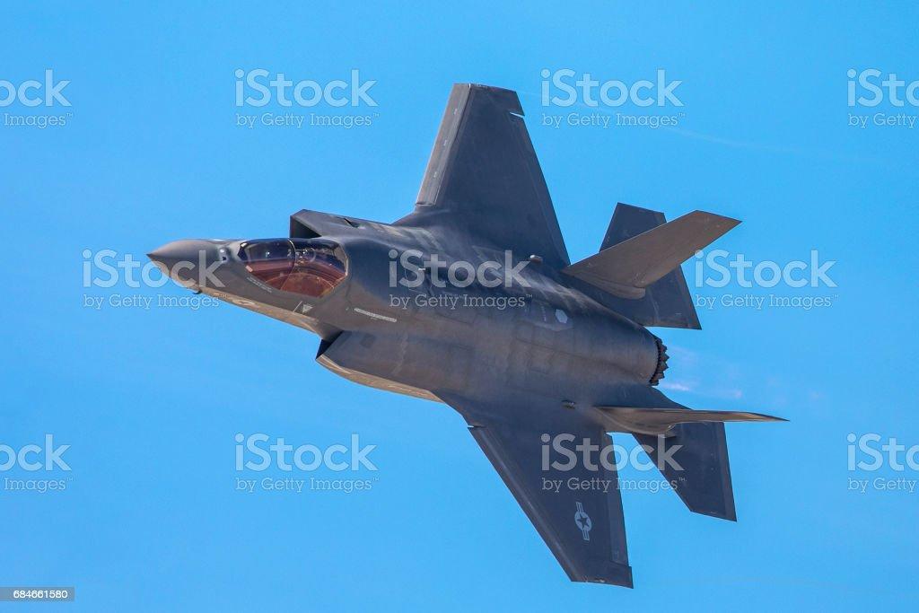Vista muy cercana de un F-35 Lightning II en una vuelta apretada, con dispositivo de poscombustión en - foto de stock