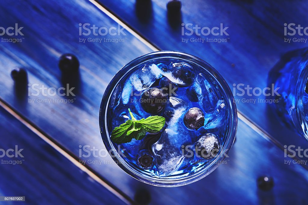 extremely colorful blueberry cocktail with mint shot top down stock photo