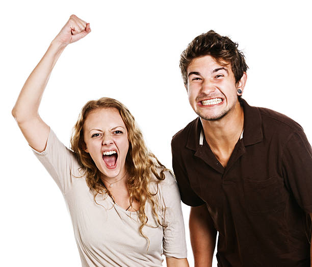 Extremely excited couple yell and gesticulate This attractive young couple are tense and stressed, grimacing, gesturing and shouting; they could be angry, excited, or involved team supporters or spectatorsor even protesting students.  Isolated on white. clenching teeth stock pictures, royalty-free photos & images