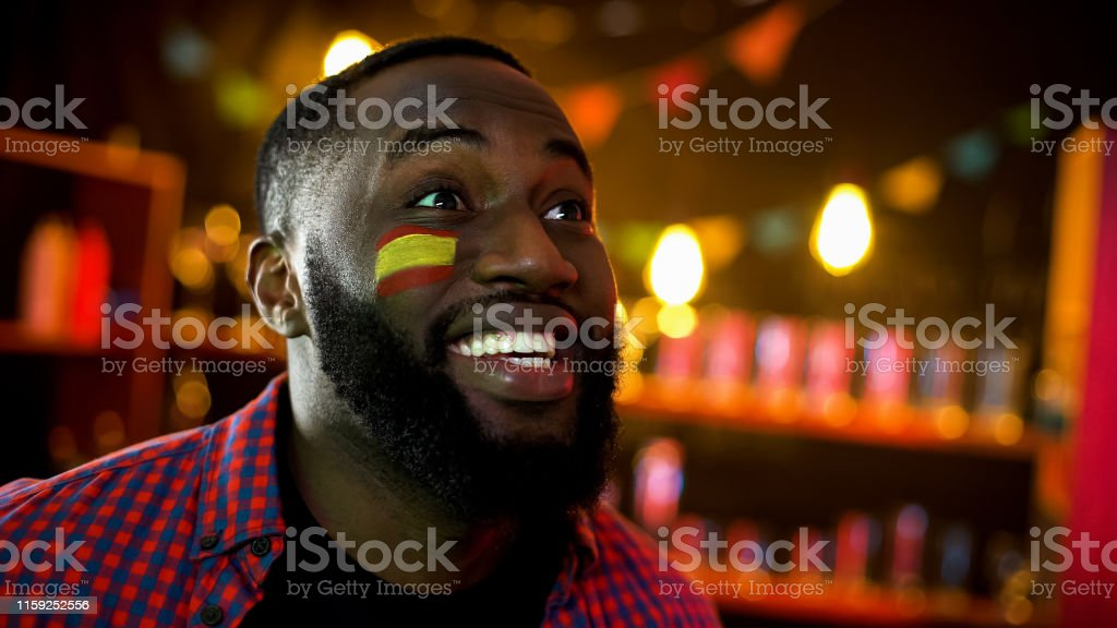 Extremely happy black spanish fan with flag on cheek shouting, team...