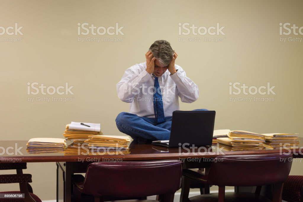 Extremely stressed out upset overworked man at work sitting on table with stacks of project folders stock photo