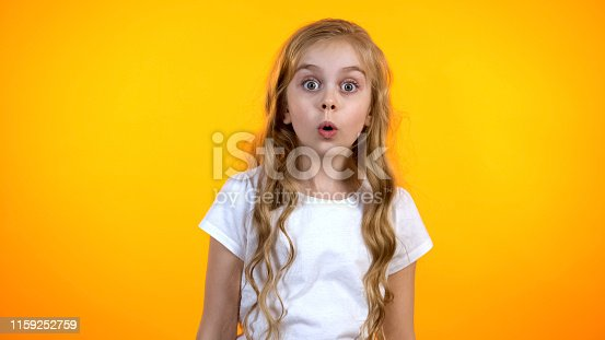 istock Extremely surprised girl with big eyes looking to cam, shocked with news, promo 1159252759