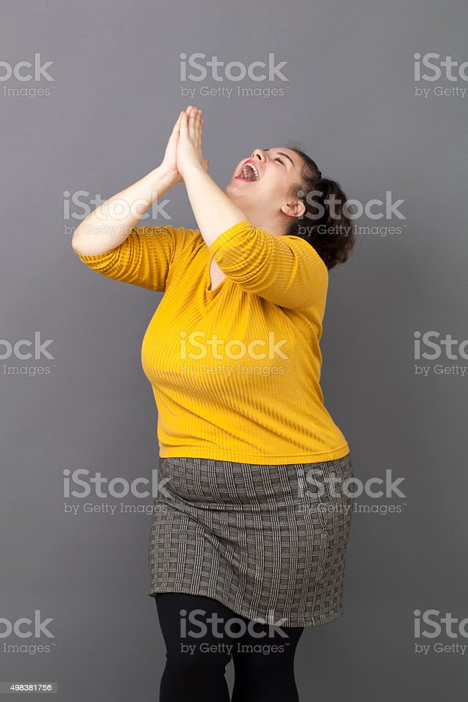 extrovert young big woman praying and celebrating her emotions stock photo