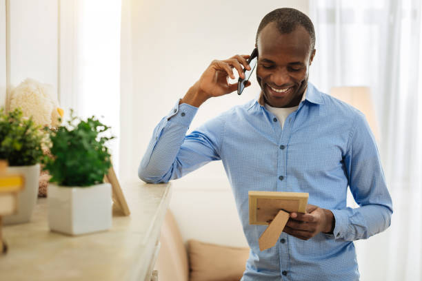 Exuberant man talking on the phone and holding a picture stock photo