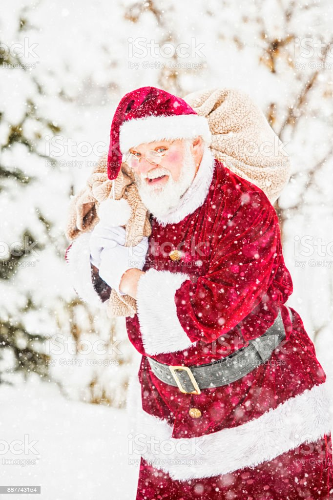 Exuberant Santa Carrying His Pack Of Toys In A Winter Storm stock photo