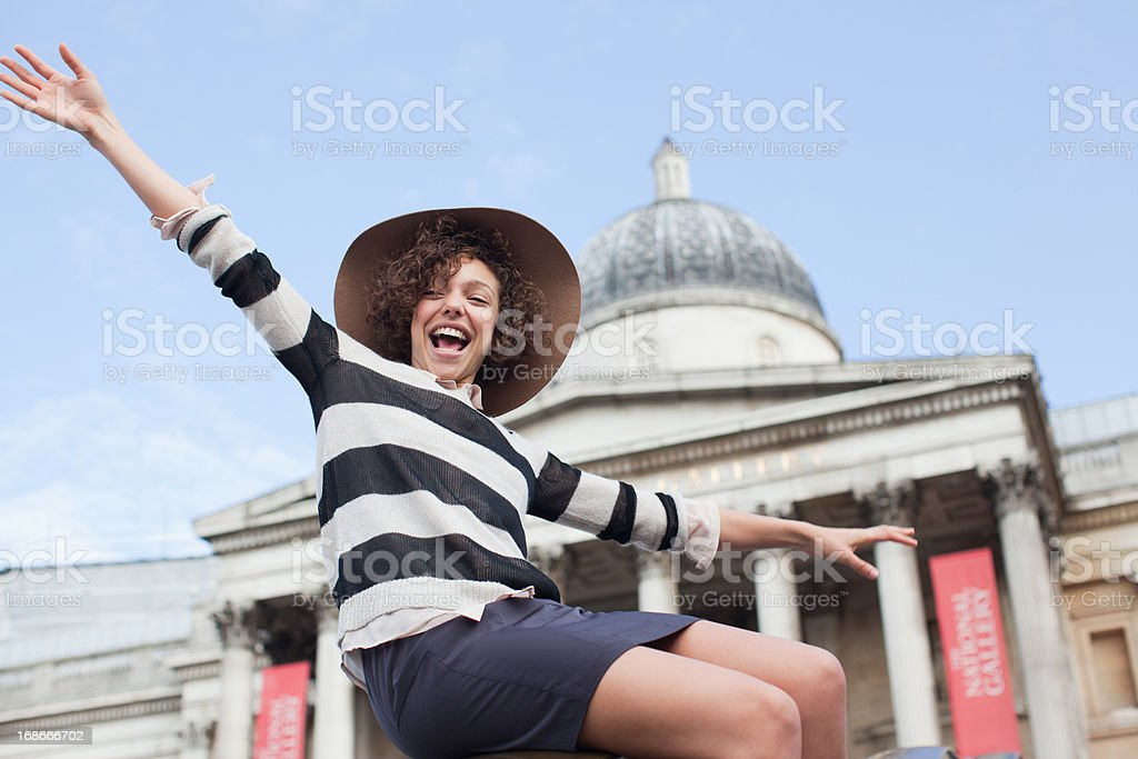 Exuberant woman in hat below historical landmark in London royalty-free stock photo