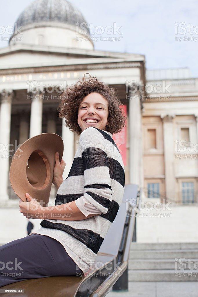 Exuberant woman with hat below historical landmark in London royalty-free stock photo