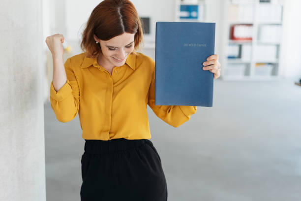 Exultant young woman celebrating getting a job stock photo