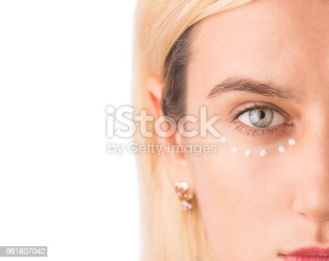 istock Eye cream treatment. Close up of green eye beautiful woman applying eye cream. Anti-aging and wrinkle eyes concept. Isolated on white 981607042