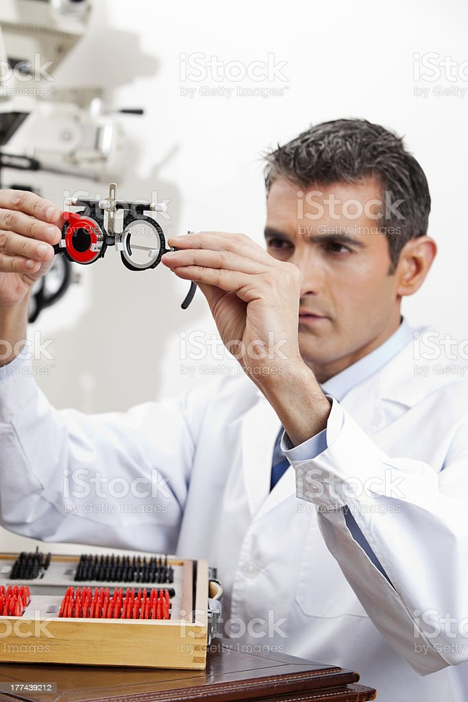 Eye Doctor Checking Lens Of Trial Frames royalty-free stock photo