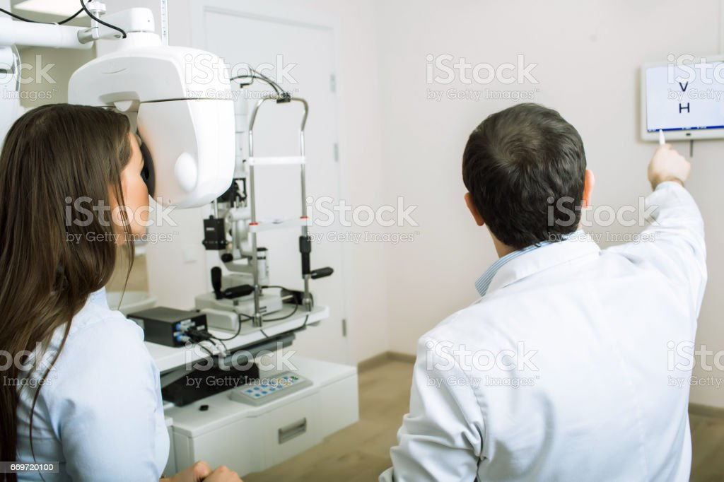 eye doctor examining female patient stock photo