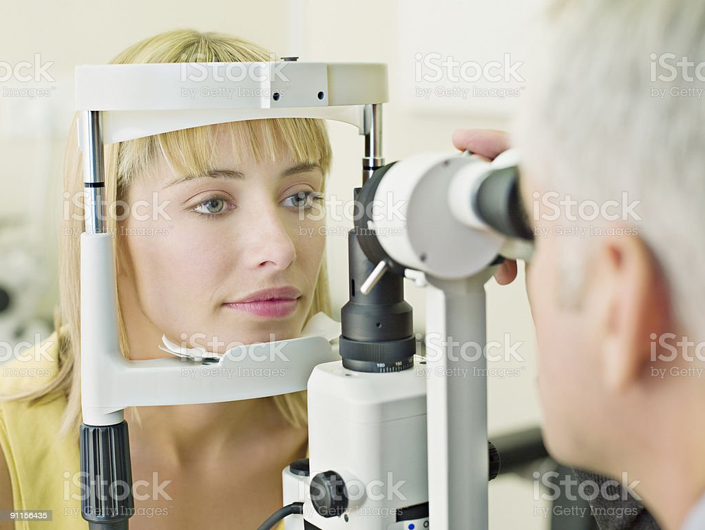 Eye doctor examining womanÕs vision stock photo