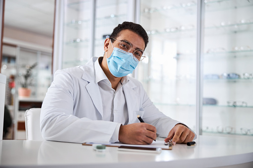 Dark-haired male ophthalmologist in a face mask and a lab coat sitting at the table