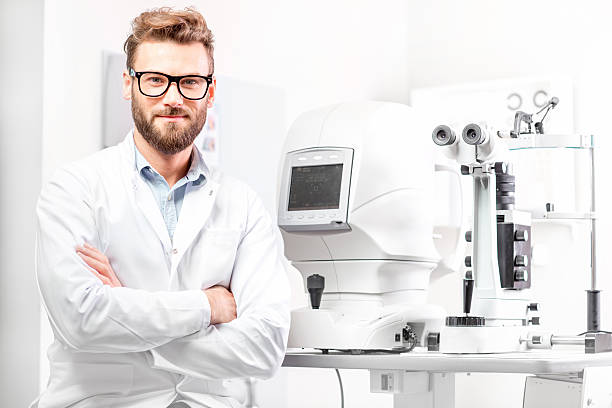 eye doctor with ophthalmologic device - optometrista - fotografias e filmes do acervo