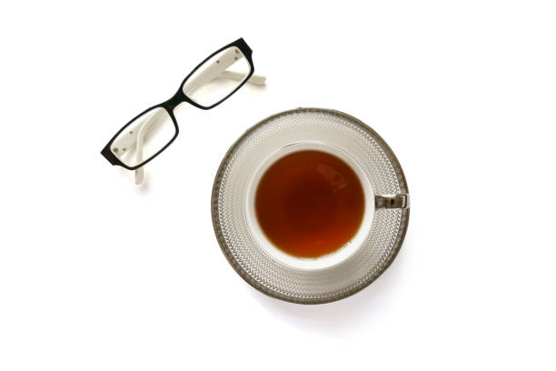 Eye glasses and a cup of tea on white background Photo of Eye glasses and a cup of tea on white background descry stock pictures, royalty-free photos & images