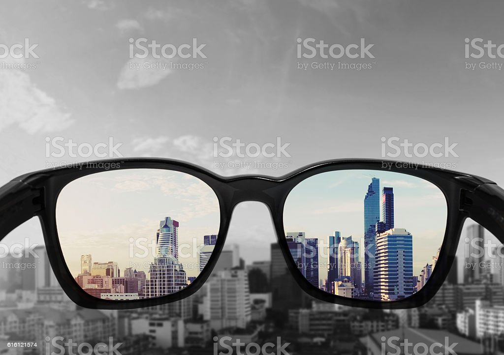 Eye glasses looking to city view, focused on glasses lens stock photo