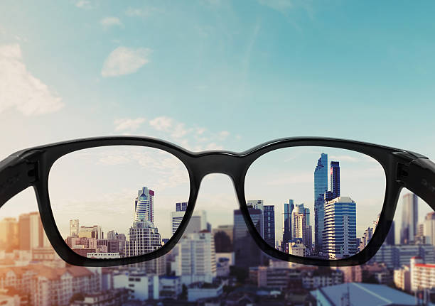 Eye glasses looking to city view, focused on glasses lens - Photo
