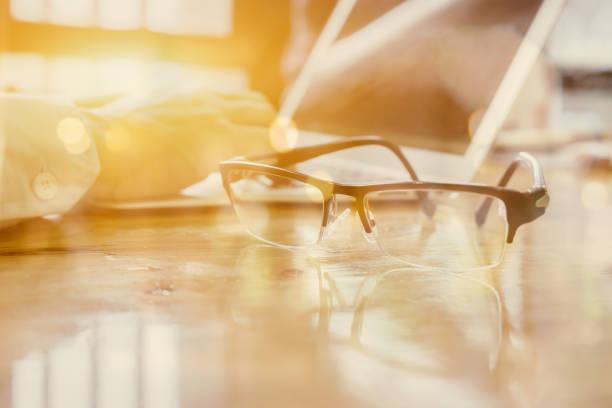 Brillen auf Geschäftsmann Holztisch mit anderen Stoffe - Tastatur, Notebook, Stift und Phone.Office Arbeitsplatz mit Laptop, Smartphone, Geschäftsmann arbeiten im Büro-Schreibtisch, Tiefenschärfe, Vintage-Ton – Foto