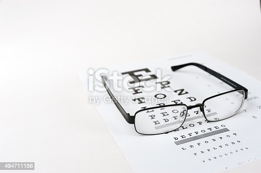 istock Eye glasses on eyesight test chart background close up 494711156
