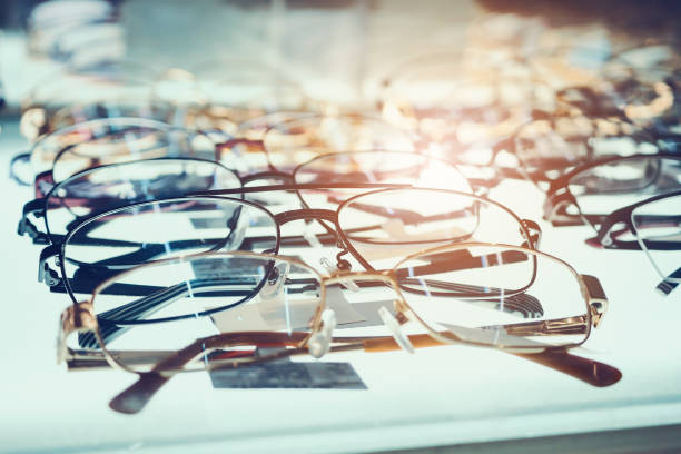 eye glasses on window display shelves in optics store - optometrist stock pictures, royalty-free photos & images
