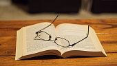 Eye glasses resting on top of a book, sitting on a wooden coffee table