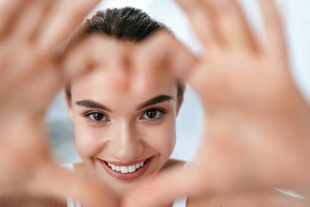 eye health. beautiful woman face with heart shaped hands. beauty - glowing stock pictures, royalty-free photos & images
