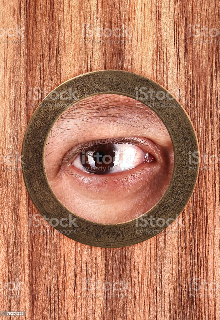 Eye is looking through peephole stock photo