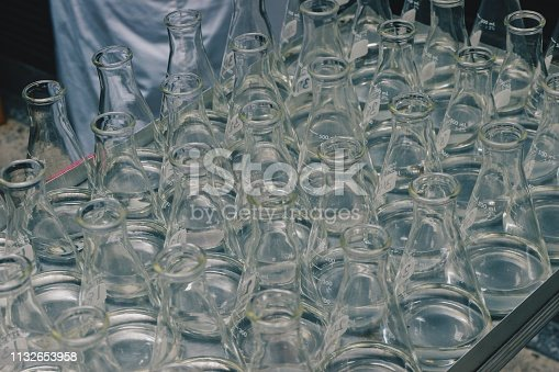 891126112istockphoto Eye level view of beaker science chemistry empty bottles or liquid put down on stainless tray at laboratory factory industrial or medical healthy care center. 1132653958