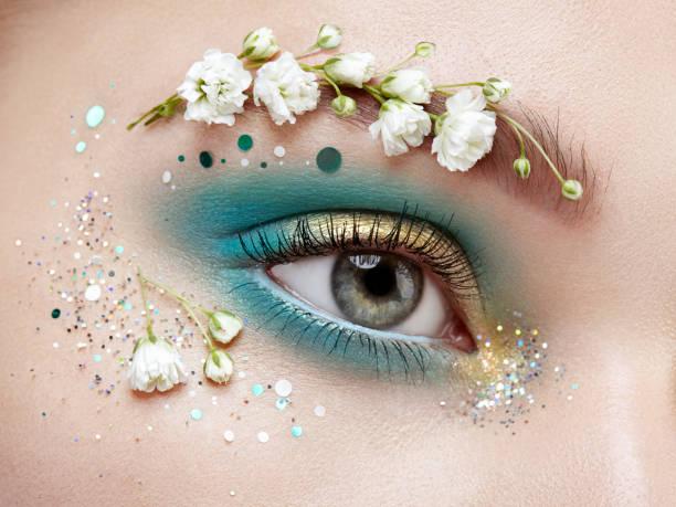 augen-make-up frau mit einer blume - blaues augen make up stock-fotos und bilder