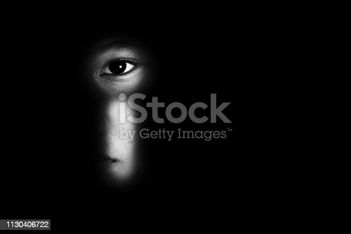 istock eye of boy through key whole, child abuse concept 1130406722