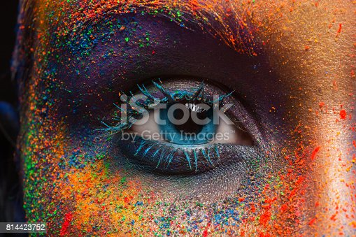 Crop of female eye with colorful make up. Beautiful fashion model with creative art makeup. Abstract colourful splash make-up. Holi festival