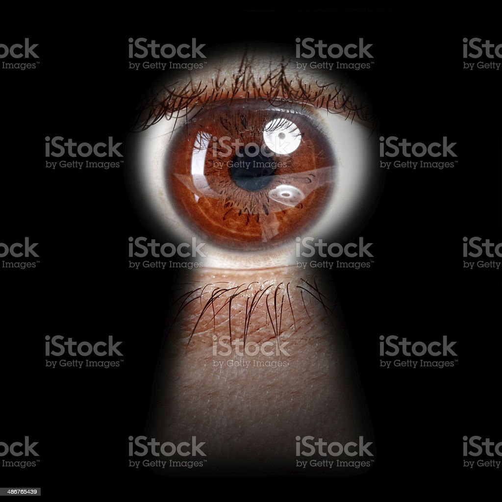 eye peeking through a keyhole stock photo
