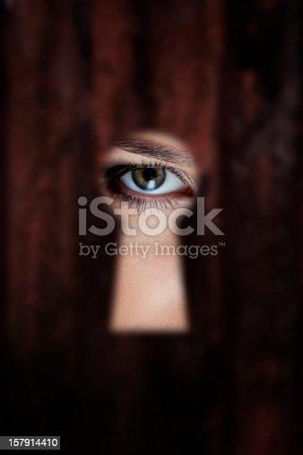 Female eye looking through a keyhole