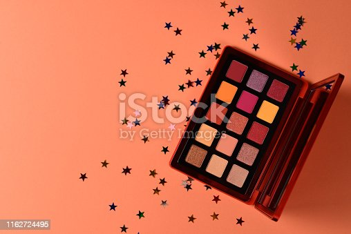 Eye shadow palette on orange background. Copy space.