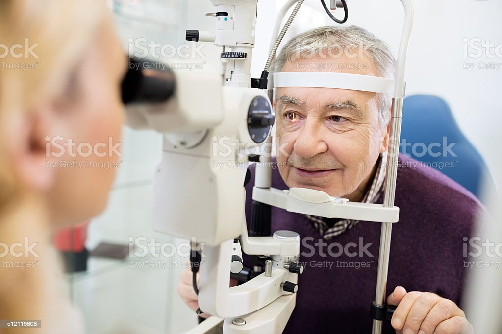 Eye specialist determines distance of eyes pupil to patient stock photo