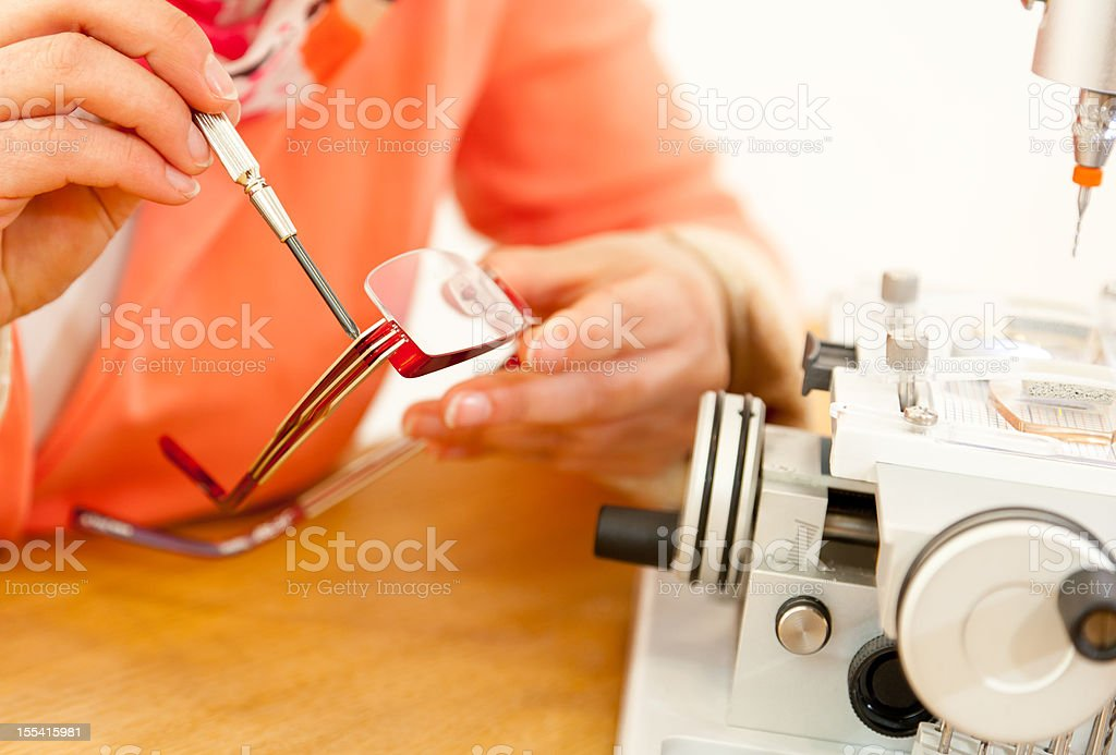 Eye technician fixing a pair of glasses with screwdriver royalty-free stock photo
