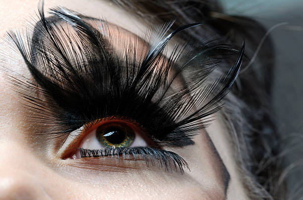 eye with feather eyelashes - gothic fashion stock photos and pictures