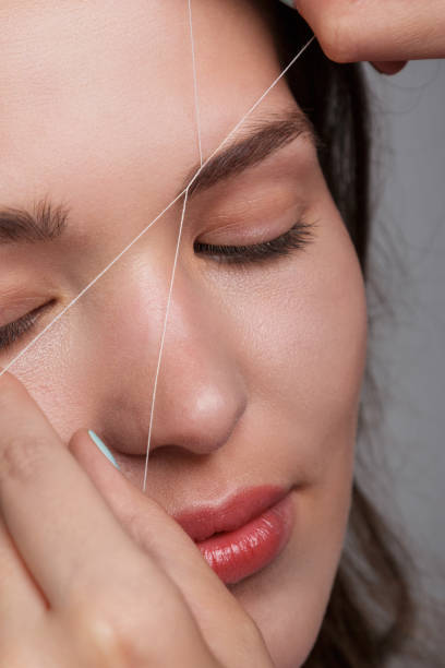 Eyebrow correction with a white thread Close-up of female face during eyebrow correction procedure threading stock pictures, royalty-free photos & images