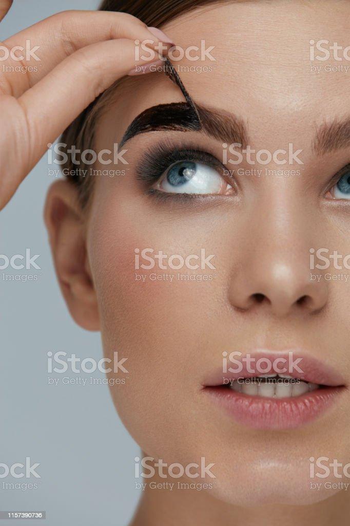 Eyebrow cosmetics. Woman taking off brow gel tint from eyebrow...