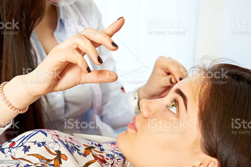 Eyebrow thread correction stock photo