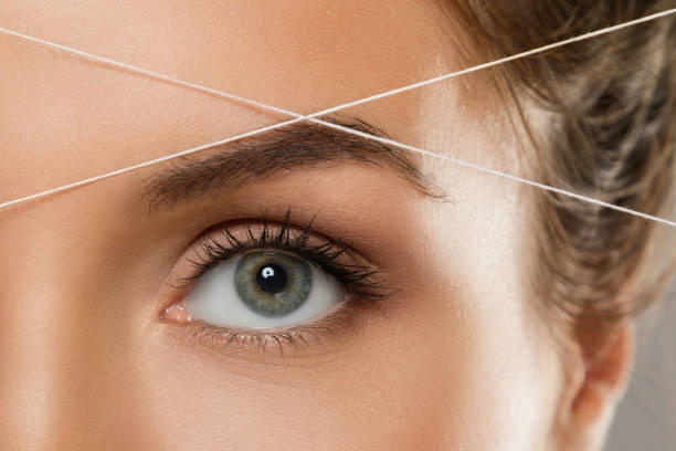 Eyebrow threading - epilation procedure for brow shape correction Close-up of female eye with a thread. Eyebrow threading - epilation procedure for brow shape correction threading stock pictures, royalty-free photos & images