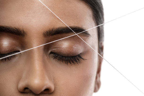 Eyebrow threading - epilation procedure for brow shape correction Close-up of Indian woman face with a thread. Eyebrow threading - epilation procedure for brow shape correction threading stock pictures, royalty-free photos & images