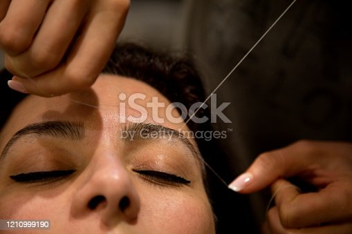Professional eyebrow hair removal service on a woman in a hair salon.