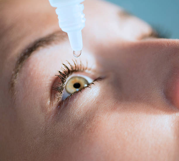 eyedropper releasing fluid into an eye - dry stock photos and pictures