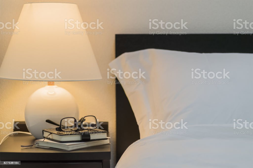 Eyeglass and book on bedside table at night stock photo
