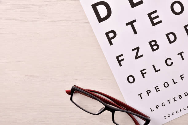 Anteojos y letra del alfabeto en la parte superior de la mesa de madera ver - foto de stock
