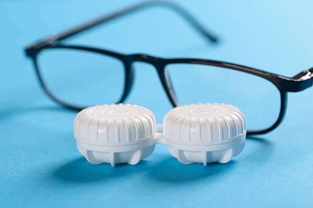 eyeglasses und lens cas'on blue background - blaue kontaktlinsen stock-fotos und bilder